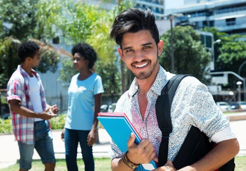 Estudante masculino latin elegante exterior no terreno com amigos fotografia de stock