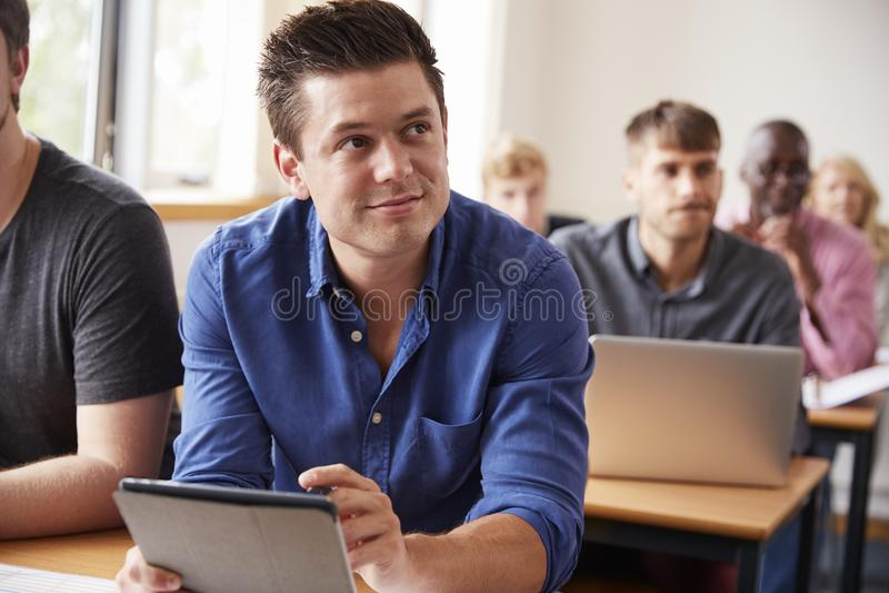 Estudante masculino maduro With Digital Tablet na classe do ensino para adultos fotos de stock royalty free