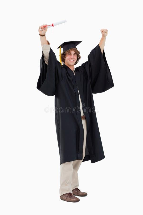 Estudante masculino na veste graduada que aumenta seus braços imagens de stock