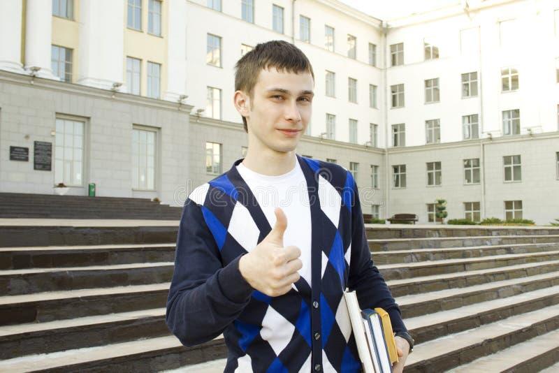 Estudante masculino no terreno com livros de texto. Polegares acima fotografia de stock royalty free