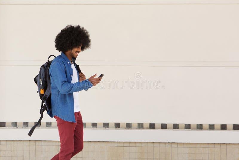 Estudante masculino que anda com saco e telefone celular fotos de stock royalty free