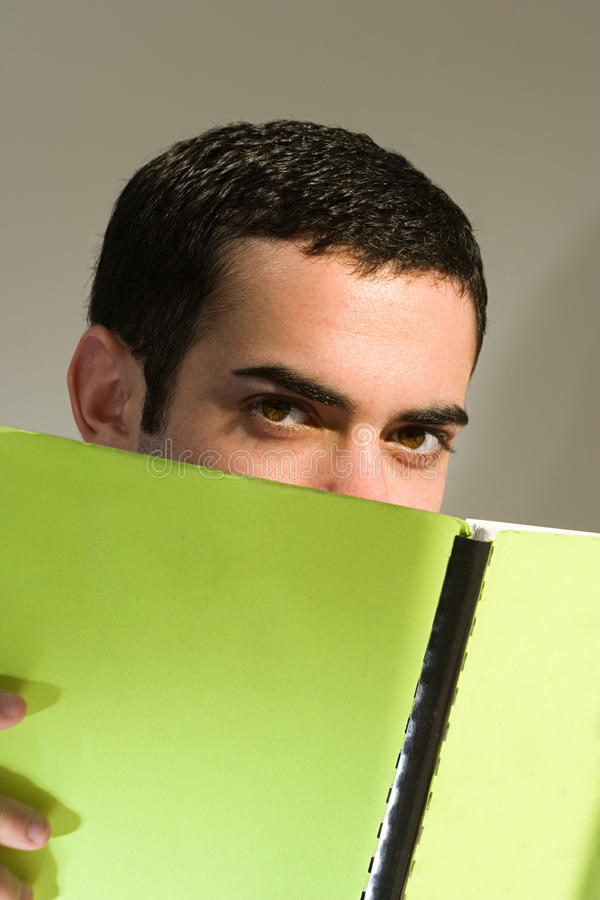 Estudante masculino que esconde atrás de um livro fotografia de stock royalty free