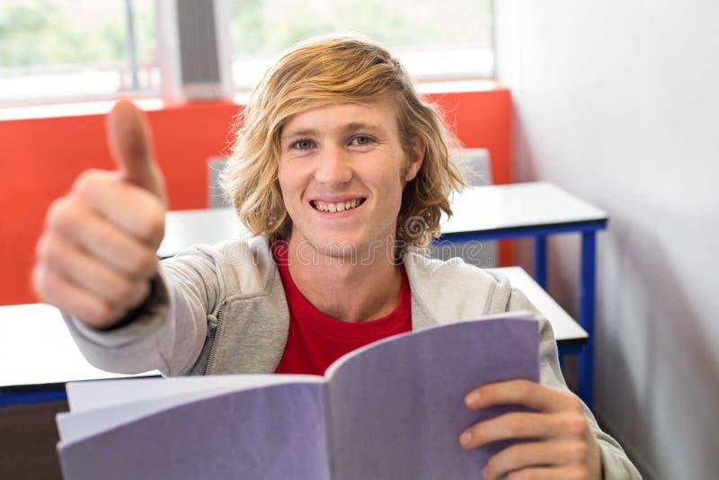 Estudante masculino que gesticula os polegares acima na sala de aula fotografia de stock