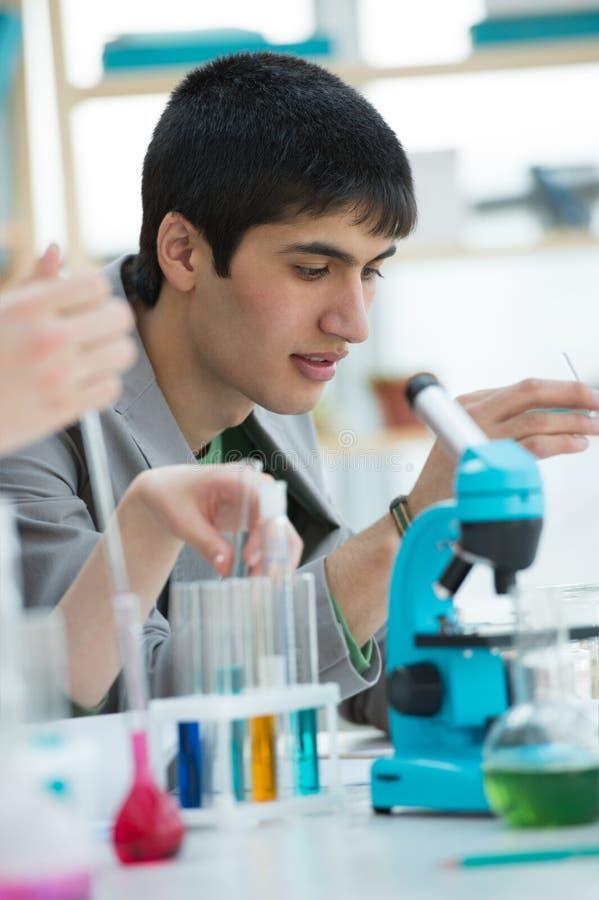 Estudante masculino que trabalha com microscópio imagens de stock royalty free