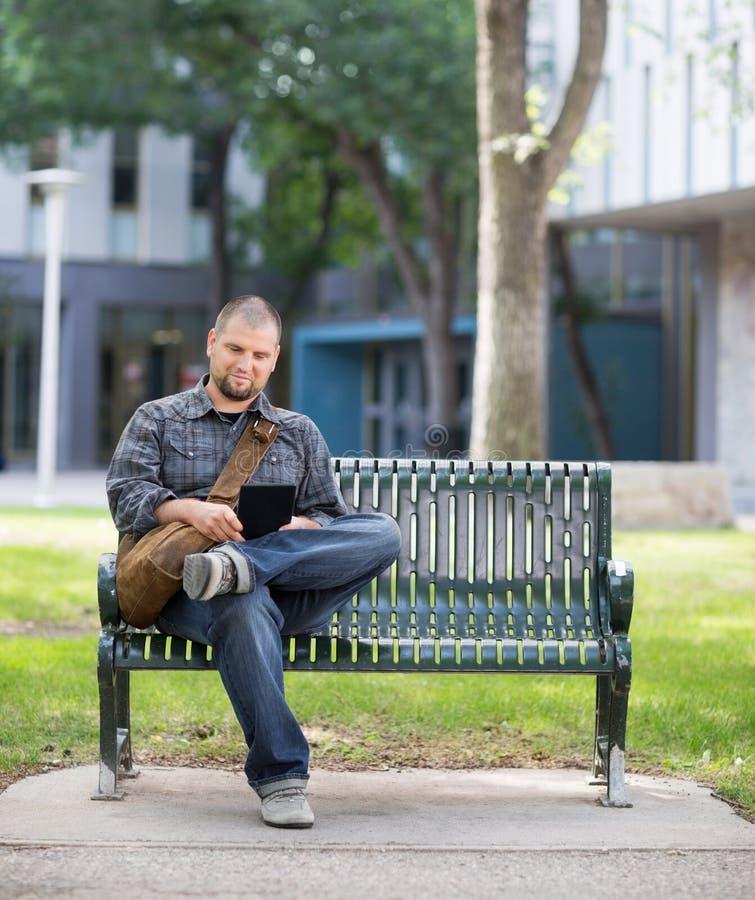 Estudante masculino Using Digital Tablet no banco em foto de stock royalty free