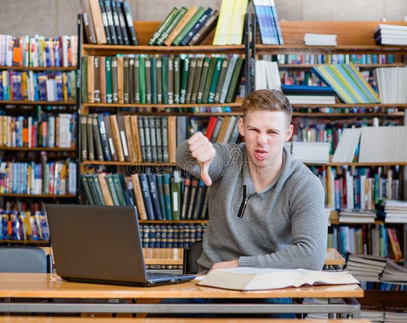 Estudante masculino virado com na biblioteca que mostra o polegar para baixo fotos de stock