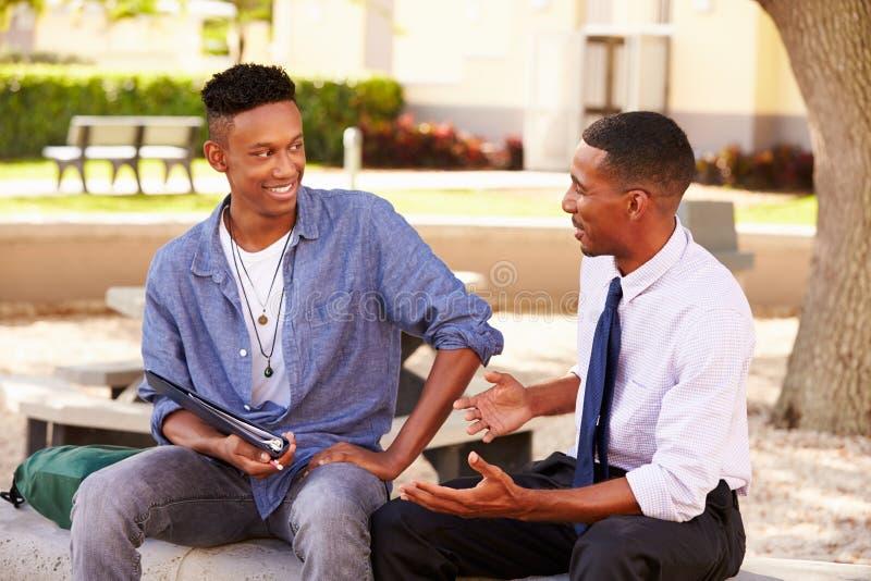 Estudante masculino With Work de Sitting Outdoors Helping do professor foto de stock