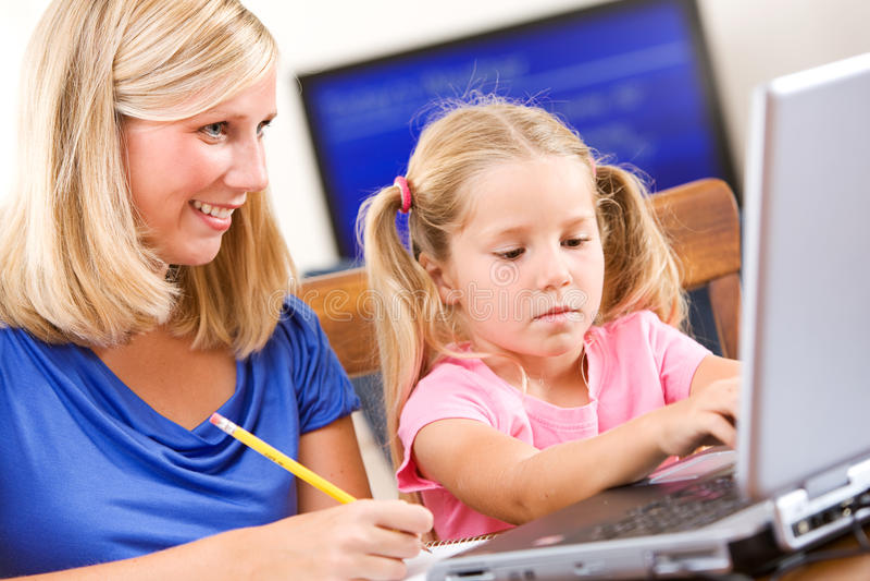 Estudante: A menina de ajuda da mãe faz trabalhos de casa no portátil foto de stock