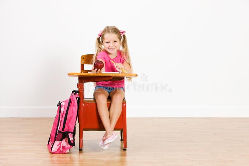 Estudante: A menina de sorriso guarda para fora Apple à câmera fotografia de stock royalty free