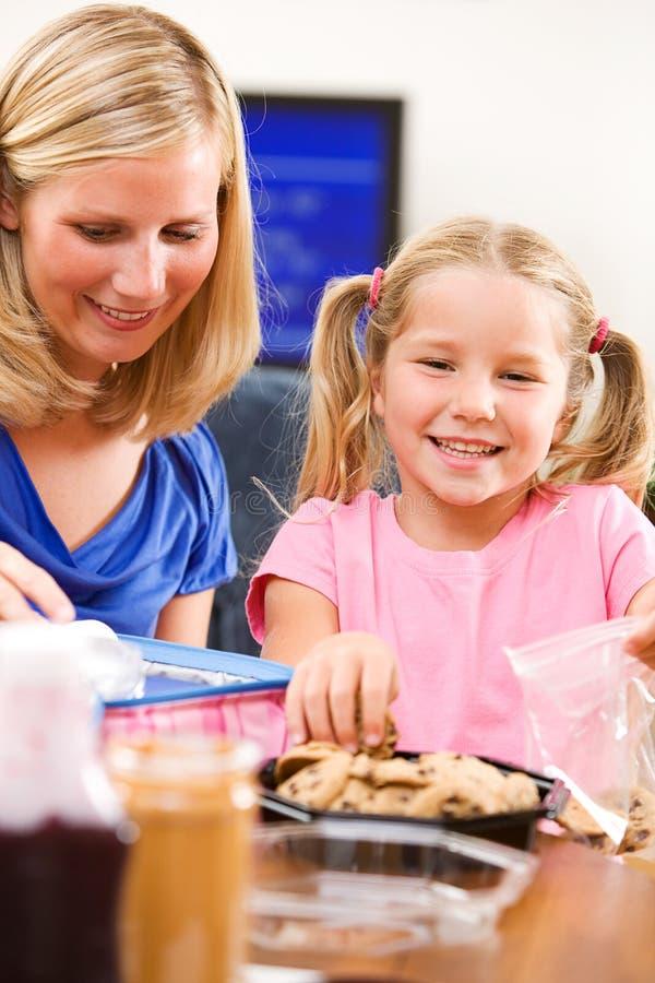 Estudante: A menina e a mãe puseram toques finais no almoço escolar fotos de stock