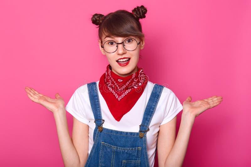 Estudante moreno novo na confusão, suporte com a boca aberta isolada sobre o fundo cor-de-rosa A estudante com dois grupos engraç fotos de stock royalty free