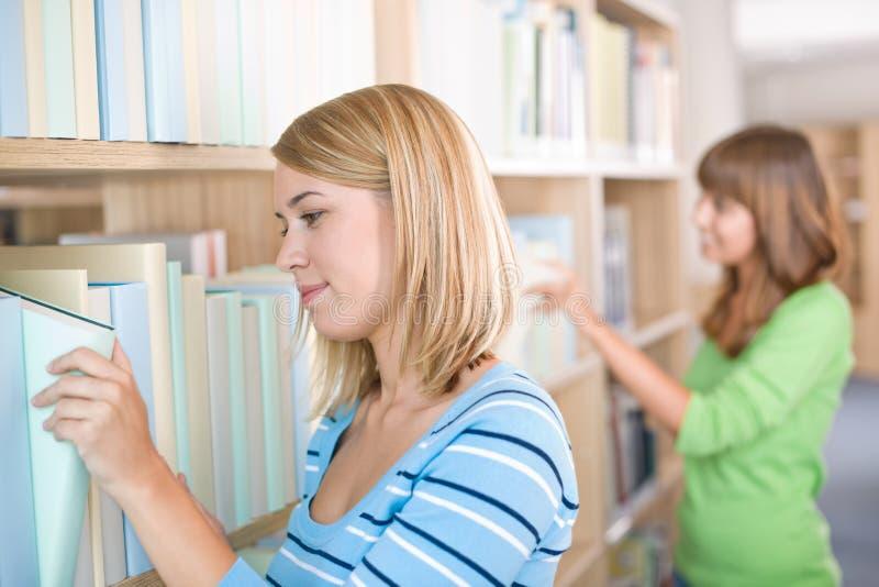 Estudante na biblioteca - busca de duas mulheres para o livro imagens de stock