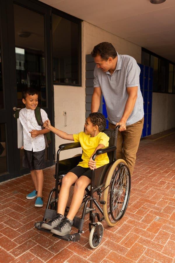 Estudante na cadeira de rodas com professor masculino e colega no corredor imagem de stock royalty free