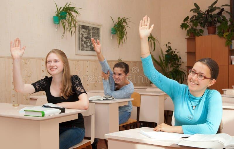 A estudante na classe levantou suas mãos fotos de stock royalty free