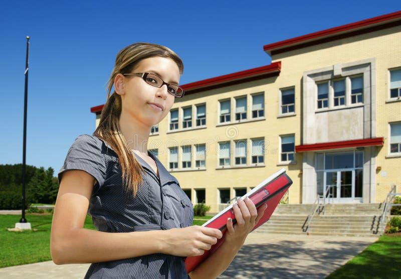Estudante na frente da entrada da escola imagem de stock royalty free