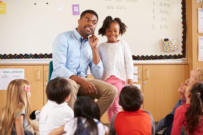 Estudante na parte dianteira da classe elementar com professor imagens de stock royalty free