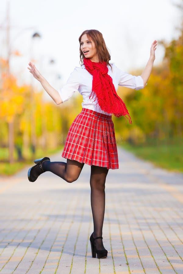 Estudante na saia vermelha, na blusa branca e no lenço foto de stock