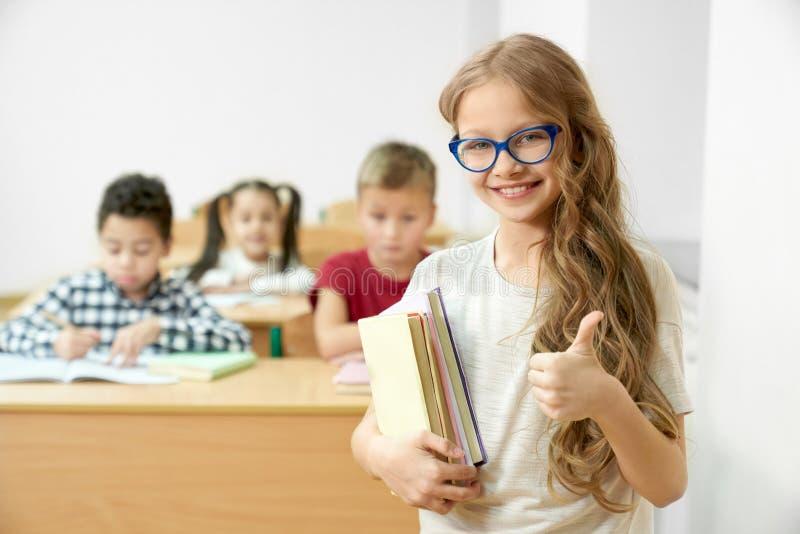 Estudante na sala de aula que guarda os livros, mostrando o polegar acima imagens de stock royalty free