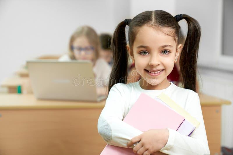Estudante na sala de aula que guarda os livros, sorrindo imagem de stock royalty free