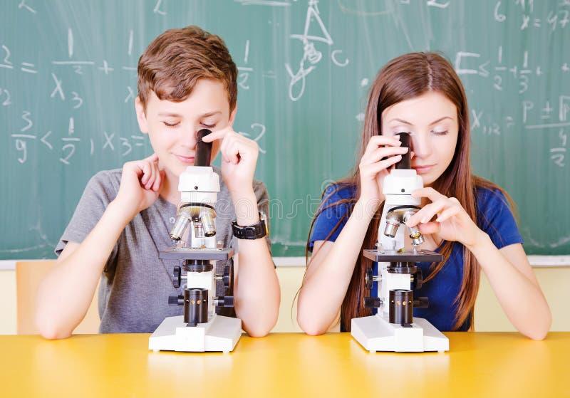 Estudante na sala de aula usando um microscópio fotos de stock