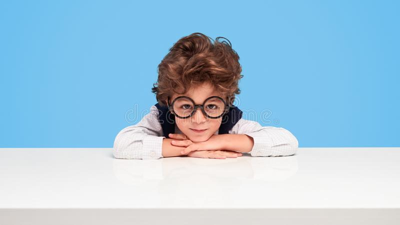 Estudante Nerdy que senta-se na mesa fotos de stock