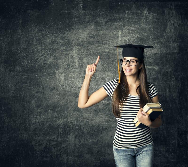 Estudante no chapéu da graduação, ponto do dedo, menina mestra nos vidros foto de stock royalty free