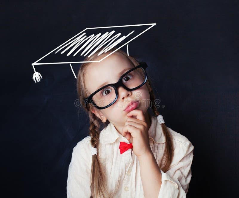 Estudante no chapéu da graduação que pensa contra o quadro fotografia de stock royalty free