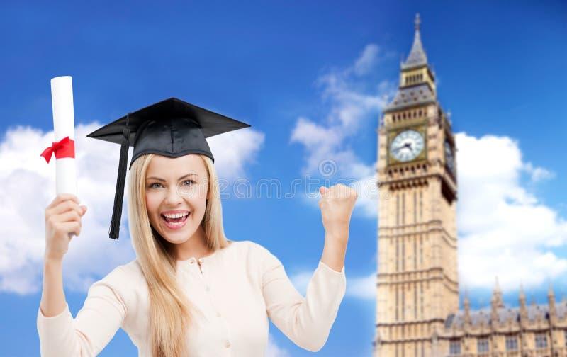 Estudante no tampão do trencher com o diploma sobre ben grande fotografia de stock