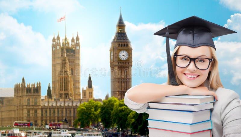 Estudante no tampão do trencher com os livros sobre Londres fotografia de stock royalty free