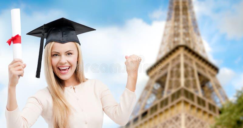 Estudante no trencher com o diploma sobre a torre Eiffel imagens de stock royalty free