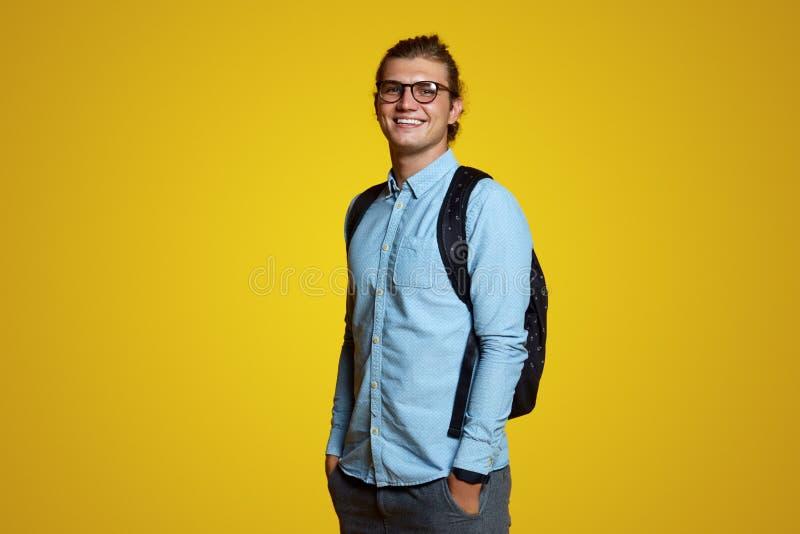 Estudante novo alegre com trouxa, a camisa ocasional azul vestindo e os monóculos, estando e rindo sobre o contexto amarelo brilh imagem de stock royalty free