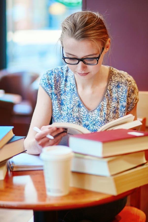 Estudante novo bonito com lotes dos livros imagens de stock
