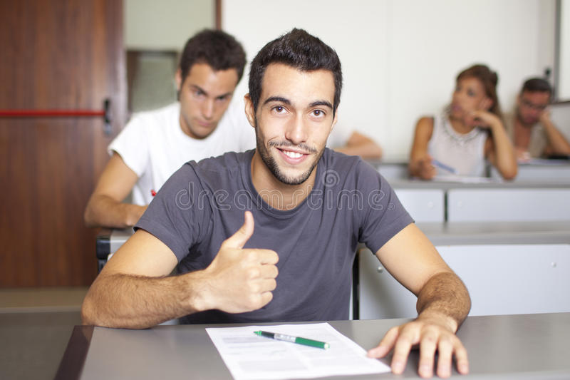 Estudante novo bonito na classe com polegar acima fotografia de stock