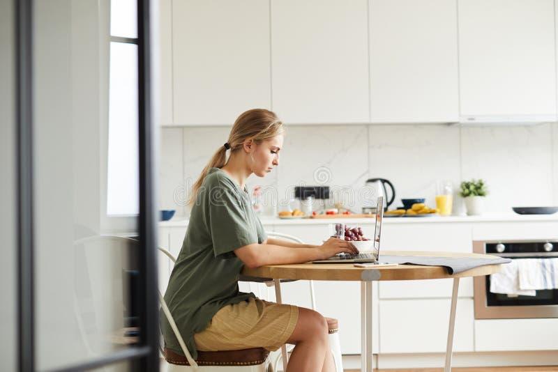 Estudante novo bonito que senta-se na cozinha na frente do portátil fotografia de stock