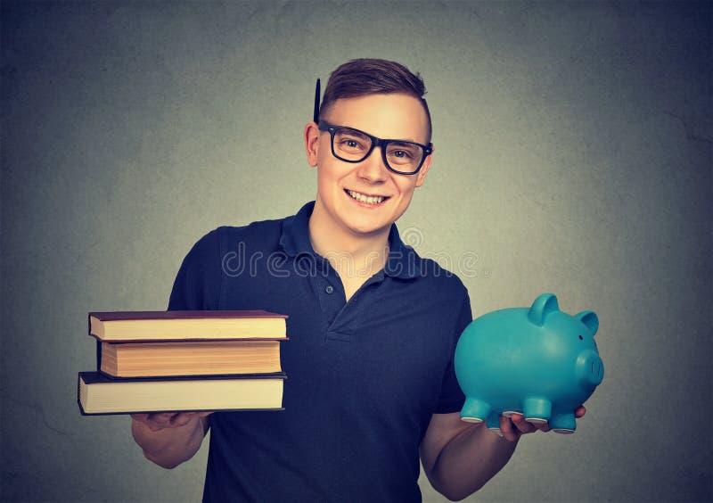 Estudante novo com livros e moneybox fotografia de stock royalty free
