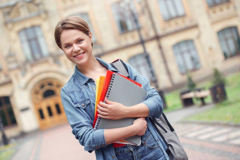 Estudante novo com a trouxa na posição do campus universitário com os livros que olham o fundo borrado amigável da câmera foto de stock royalty free