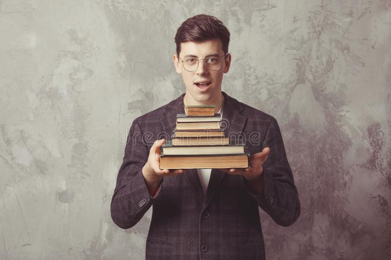Estudante novo do menino com os livros nos vidros o indivíduo feliz quer a aprendizagem e para ter a educação Educação em linha d fotografia de stock