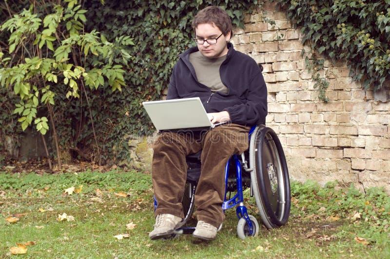 Estudante novo em uma cadeira de rodas no parque imagens de stock