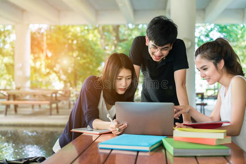 Estudante novo Group Holding Book e sorriso do laptop foto de stock royalty free