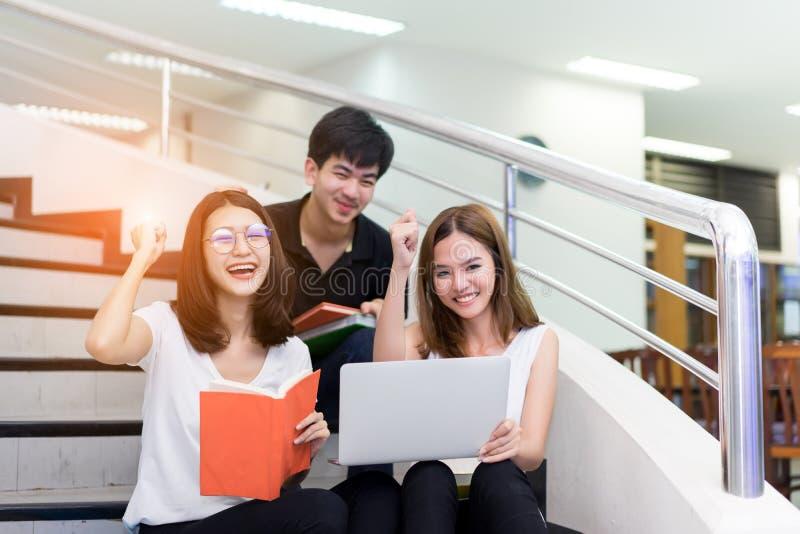 Estudante novo Group Reading Book e utilização do sorriso do laptop fotografia de stock royalty free