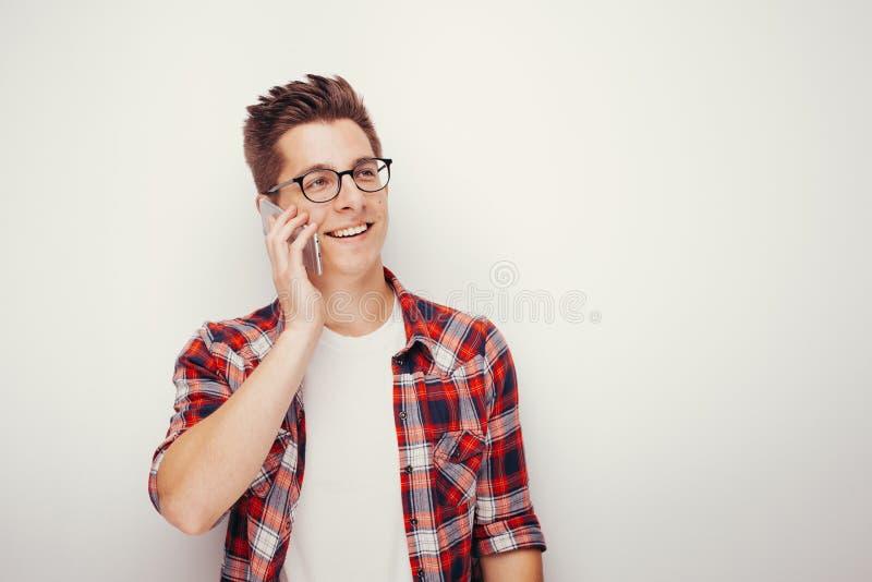 Estudante novo na camisa vermelha ocasional que fala no smartphone fotos de stock royalty free