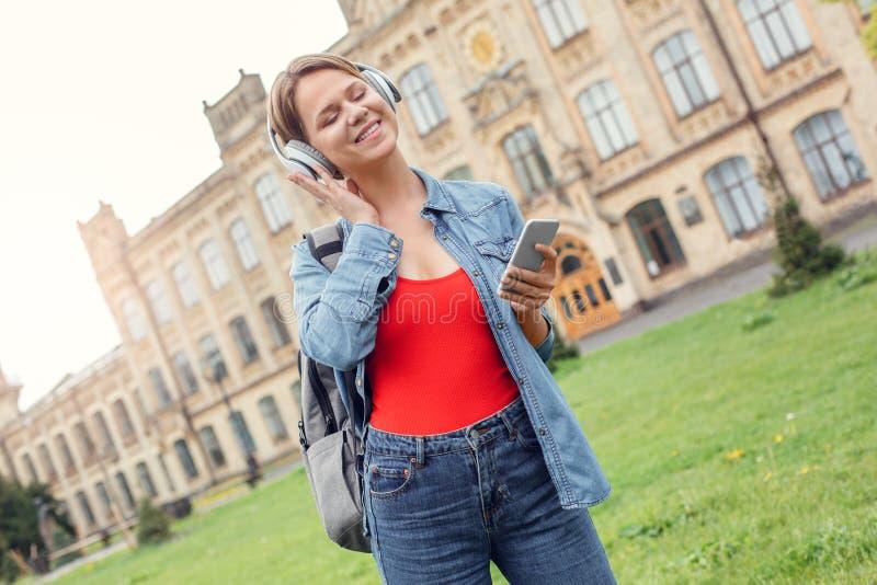 Estudante novo nos fones de ouvido que levam a trouxa no campus universitário com a música de escuta do smartphone alegre imagens de stock royalty free