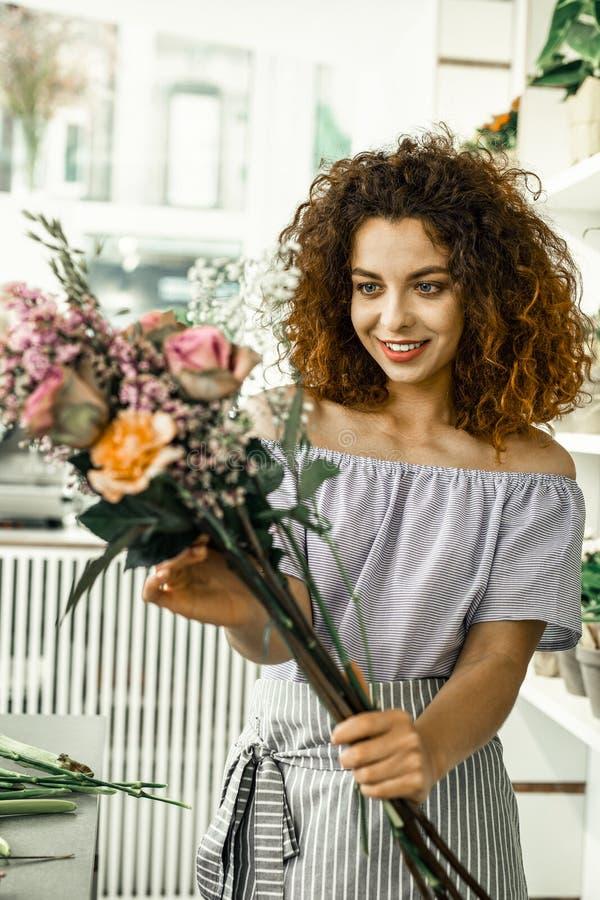 Estudante novo que ama seu primeiro trabalho ao trabalhar na loja floral fotos de stock