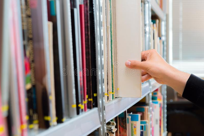 Estudante novo que escolhe um livro da prateleira na biblioteca Preparando-se para exames, homem novo que procura por ou que esco foto de stock royalty free