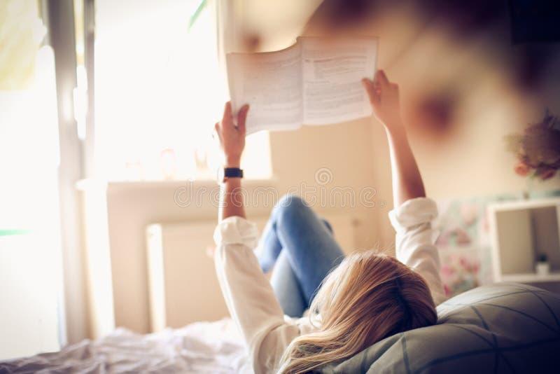 Estudante novo que lê um livro na cama imagem de stock royalty free