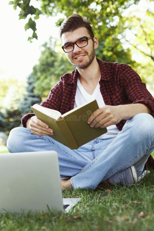 Estudante novo que prepara-se para exames fora foto de stock