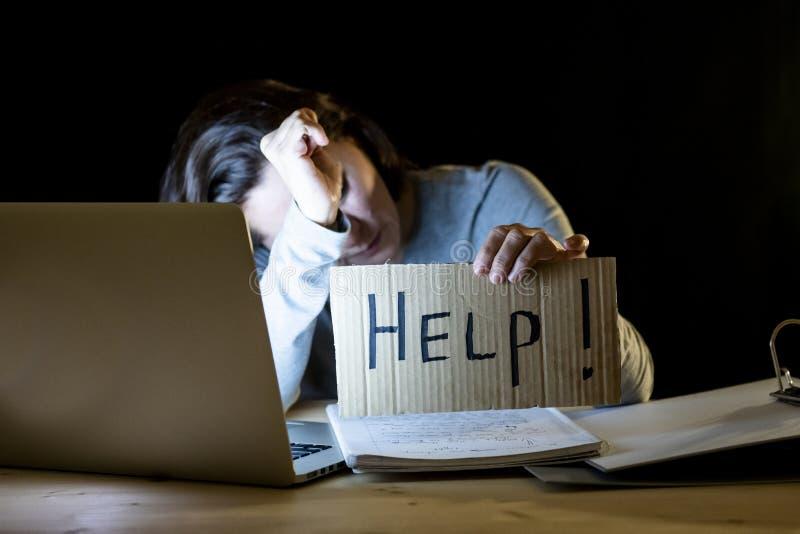 Estudante novo que trabalha tarde na noite em seu computador que guarda um sinal da ajuda fotografia de stock