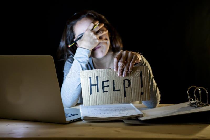 Estudante novo que trabalha tarde na noite em seu computador que guarda um sinal da ajuda fotografia de stock royalty free