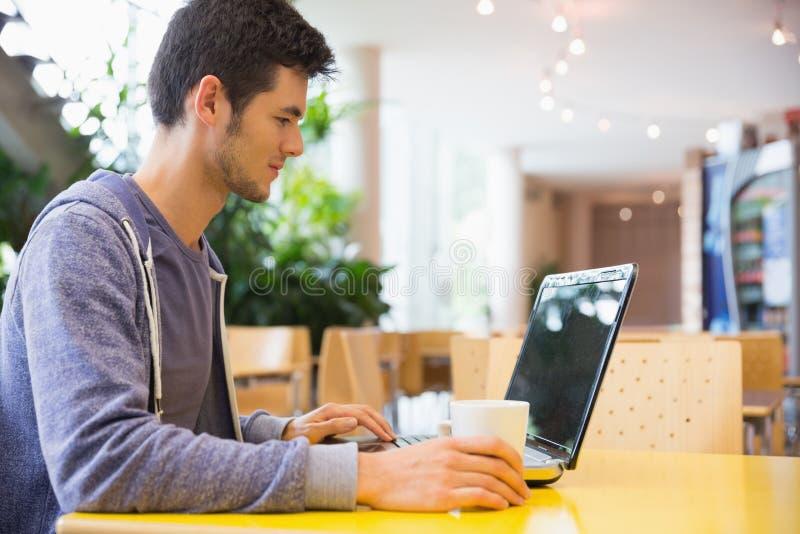 Estudante novo que usa seu portátil no café fotografia de stock