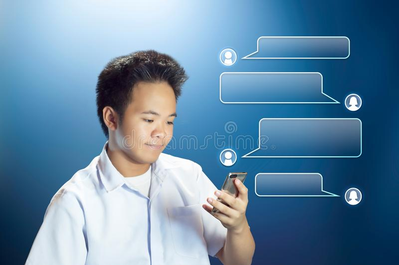 Estudante novo Texting do adolescente que usa seu Smartphone com a caixa projetada da conversação imagem de stock royalty free